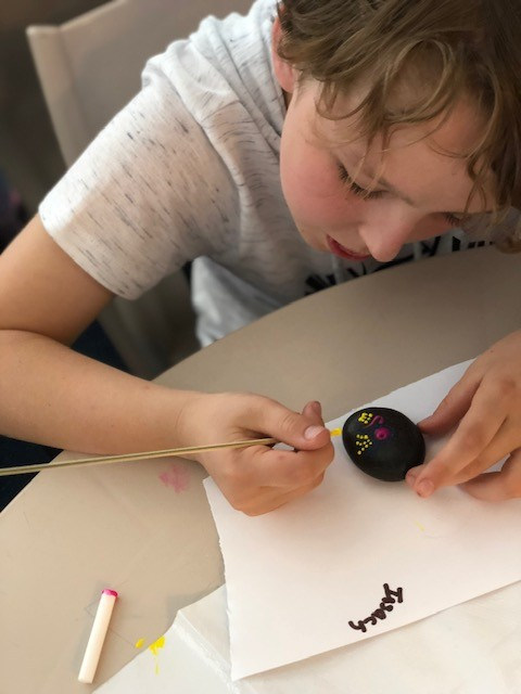 boy painting a rock with dot painting