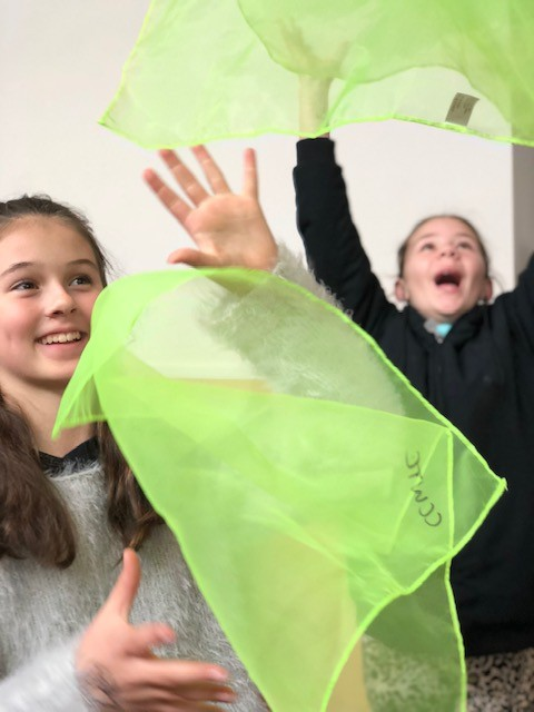two girls throwing green scarves into air