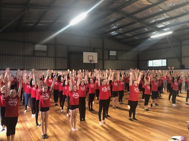 large group of students in red tshirts learning dance with hands in the air