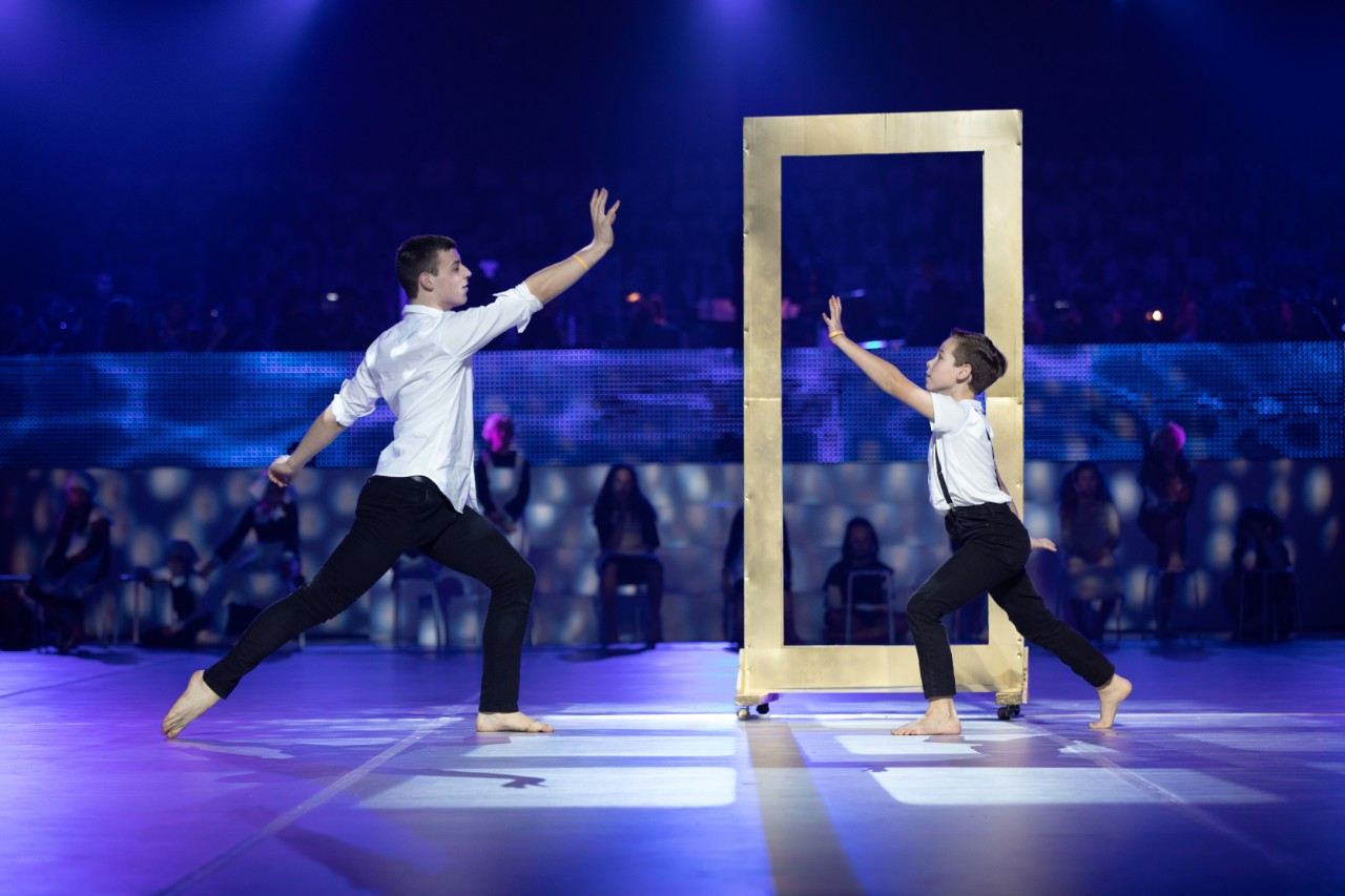 two boys dancing on stage with window frame prop