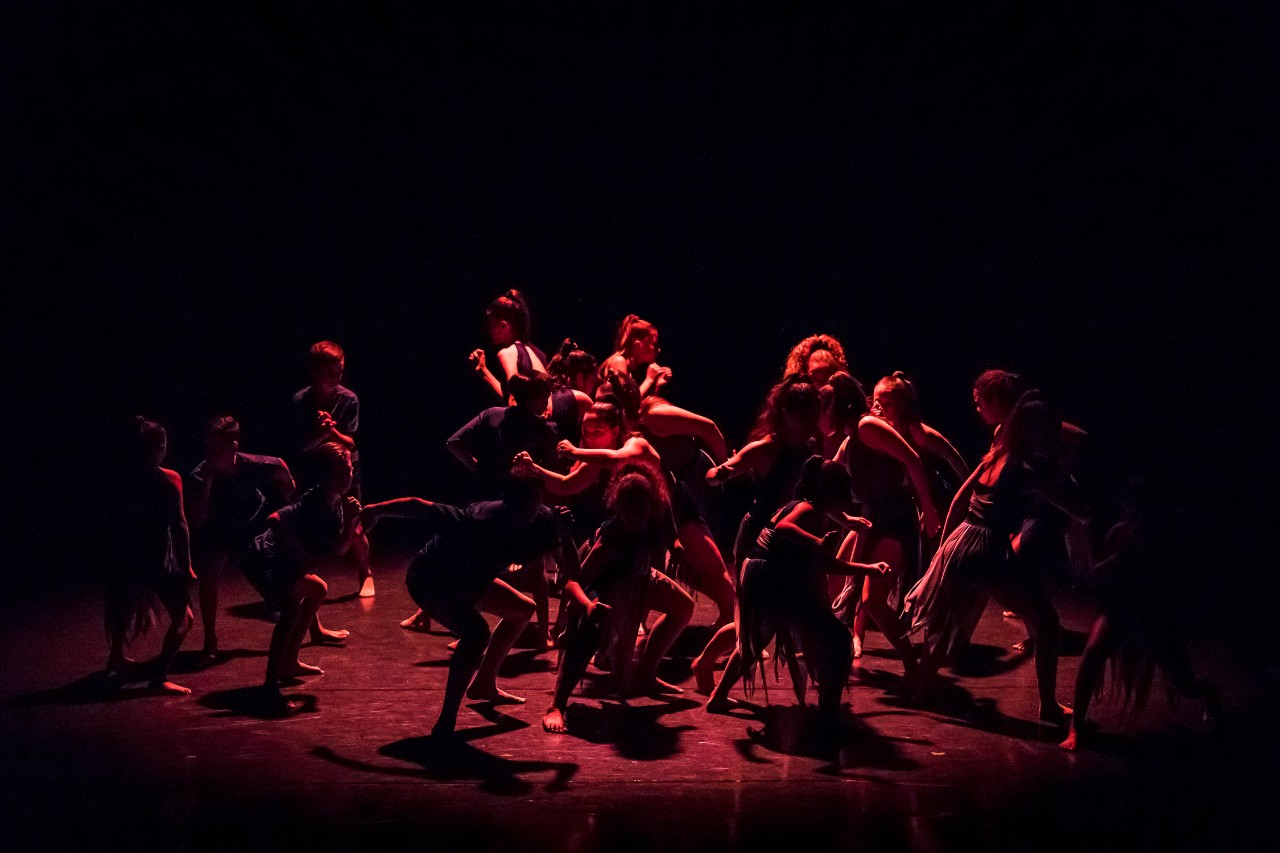troupe of dancers on stage in muted light