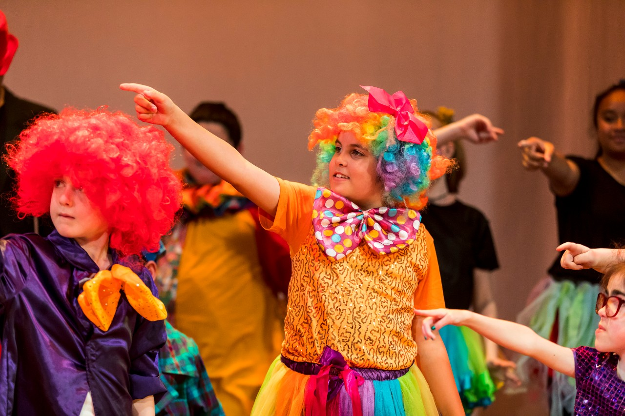 Students dancing on stage at Southern Stars showcase in clown wigs