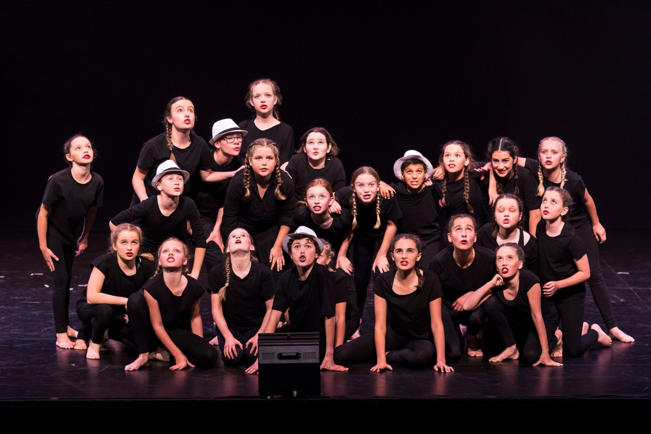 school group on stage in black tshirts performing drama item