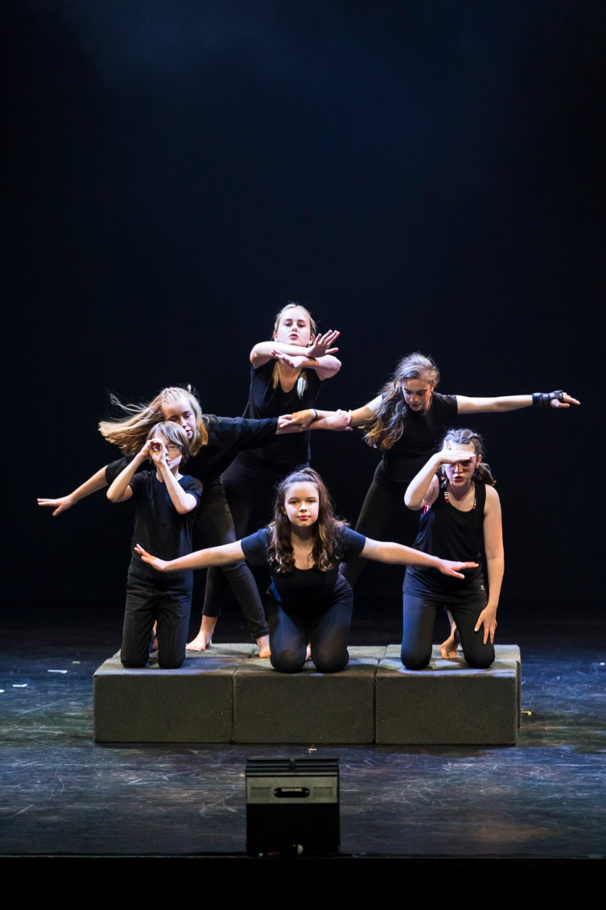 6 drama students on stage in black