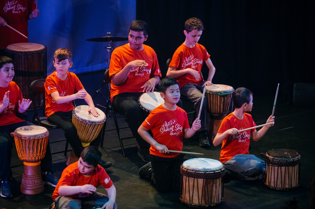 students in red t-shirts playing the drums