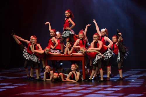 Primary dancers onstage in red. black and white costumes