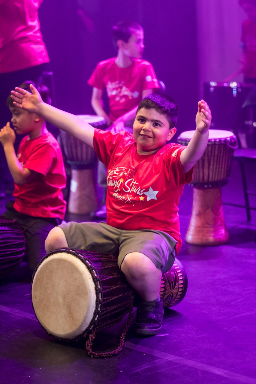 boy sitting on drum with hands up