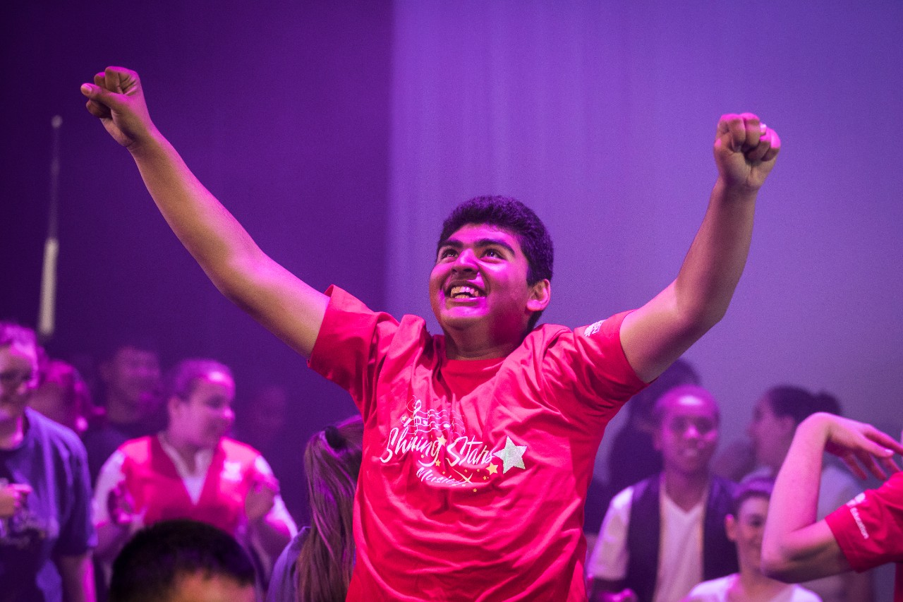 boy with arms out performing on stage in red tshirt