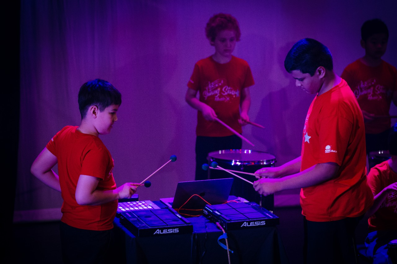 three boys playing instruments on stage in red tshirts