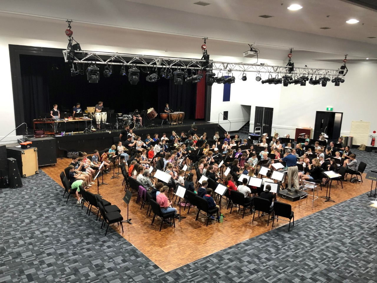 photo of band sitting in school hall playing instuments