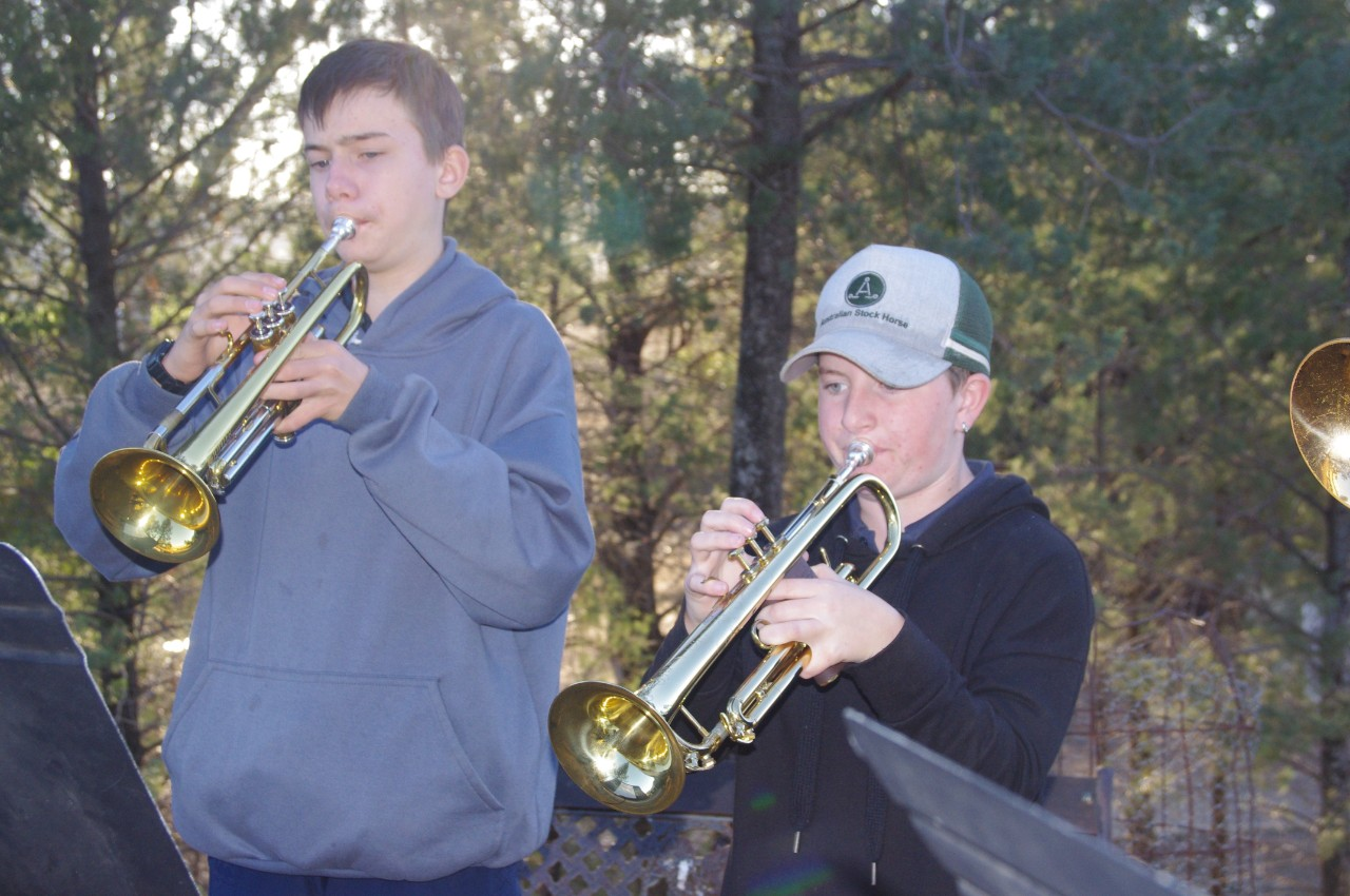 two boys playing trumpet with bush in background