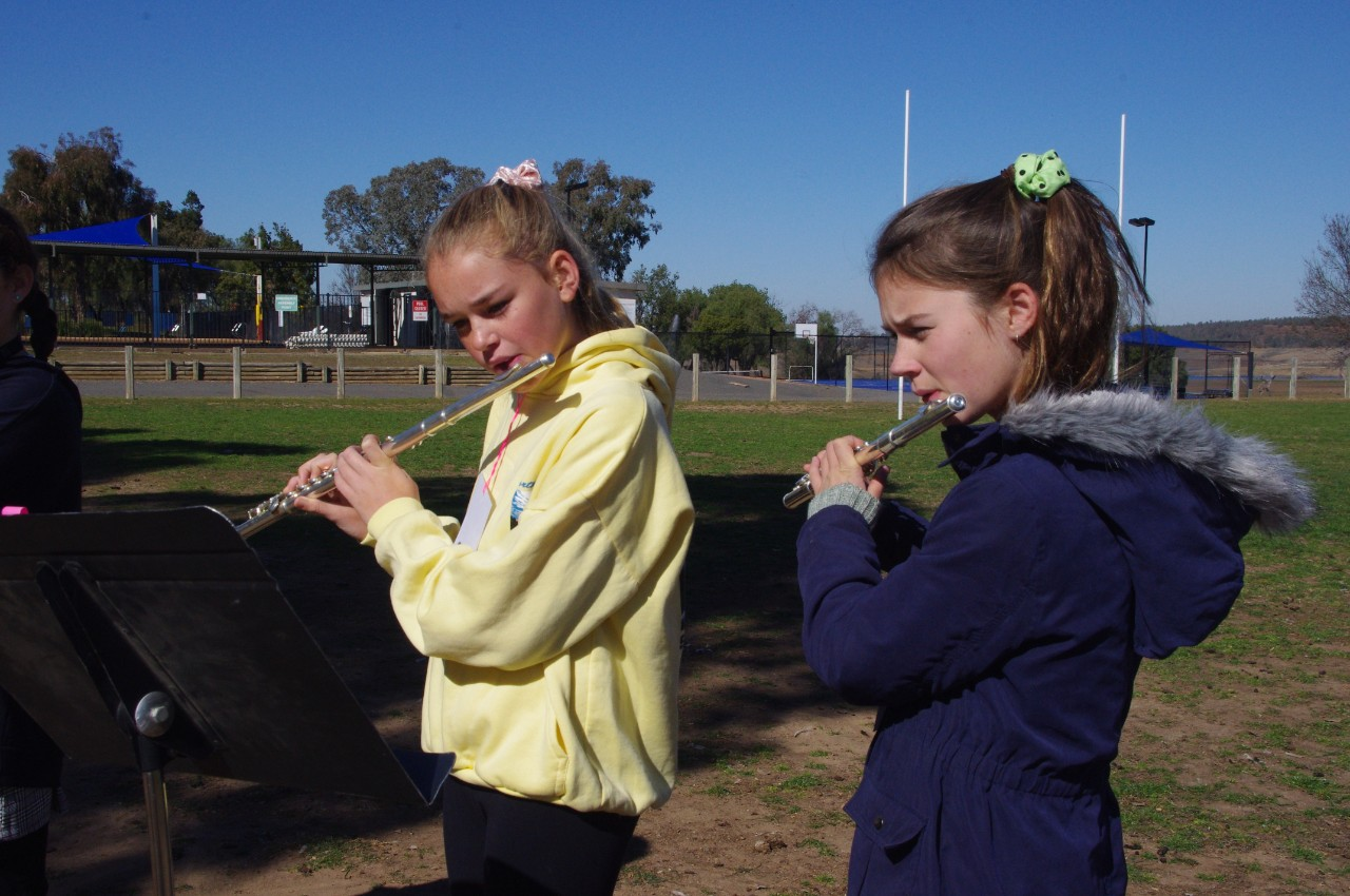two girls playing flute with camp grounds in background