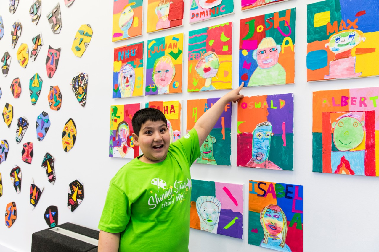 boy pointing to his artwork at Shining Stars showcase