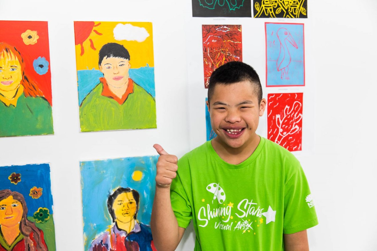 boy with thumbs up checking out his art work on the wall